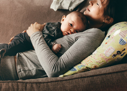 Woman lying on couch with eyes closed holding her baby