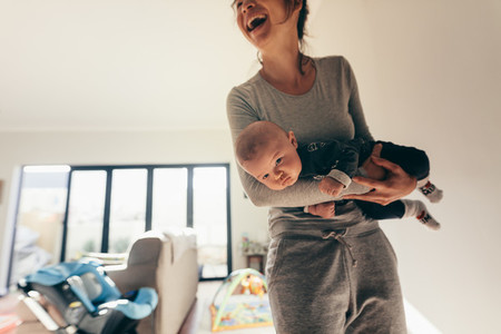 Smiling woman standing in room with her baby