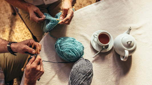 Senior people knitting at home