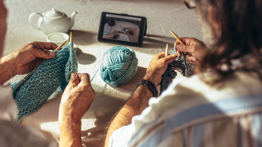 Retired people learning knitting from online videos