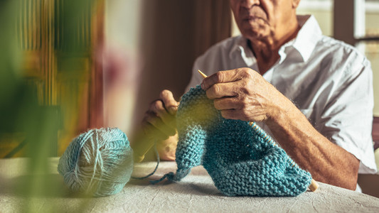 Retired man knitting at home