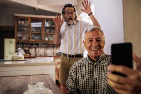 Elderly men enjoying taking selfie with mobile phone