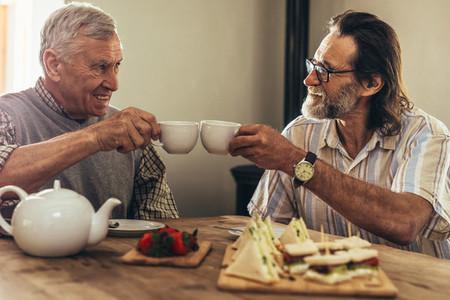 Senior men enjoying tea and snacks together at home