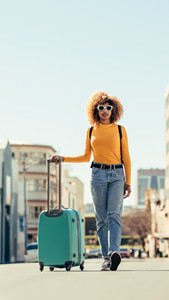 Woman tourist walking on street with luggage
