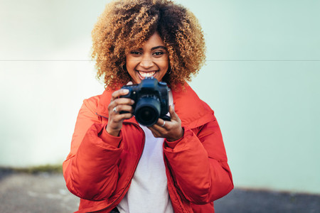Smiling woman traveller taking photos outdoors