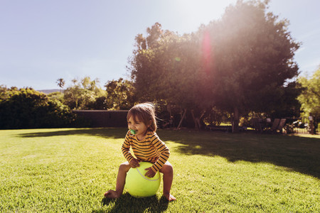 Kid sitting on a ball in a park