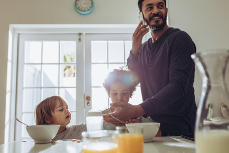 Man talking over mobile phone standing at the breakfast table