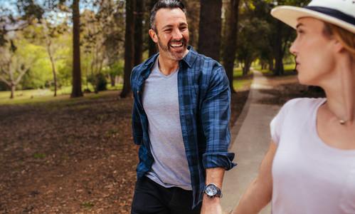 Happy couple walking through autumn park