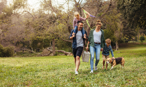 Family with dog going on picnic in park