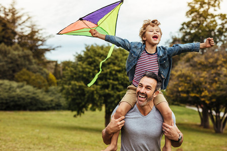 Smiling boy on fathers shoulders playing with kite