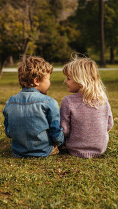 Siblings sitting on the grass and looking at each other