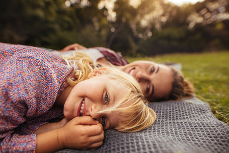 Little girl lying on picnic plaid with mother at back