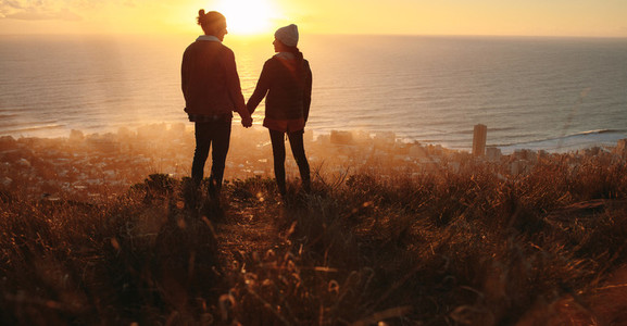 Romantic couple on peak at sunset