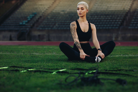 Female runner doing workout sitting in a stadium