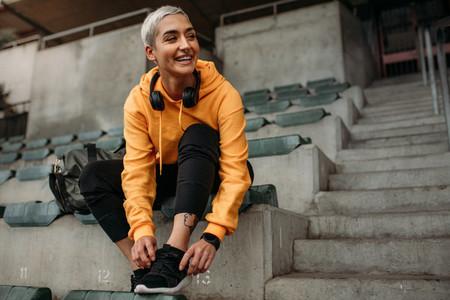 Smiling woman athlete tying shoe lace