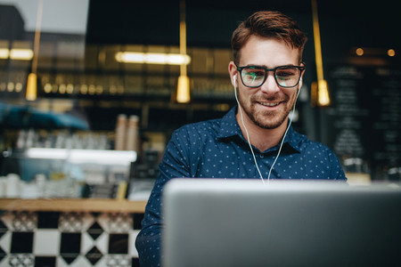Man sitting in a restaurant using laptop