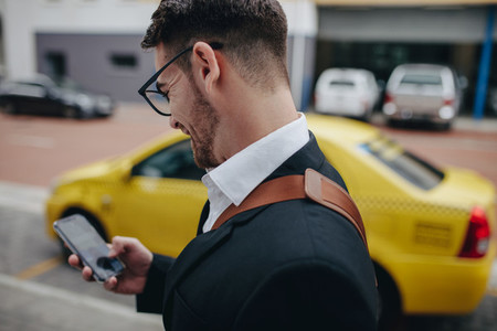 Businessman using mobile phone while walking on street