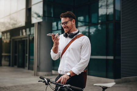 Smiling businessman talking on mobile phone standing outdoors