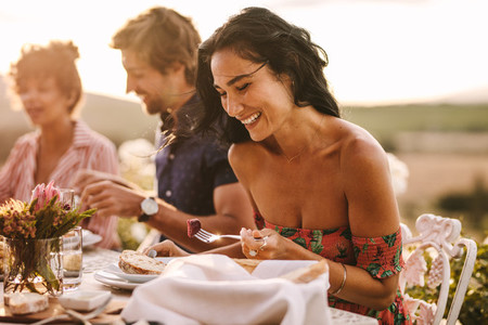 Woman enjoying having food with friends at a party