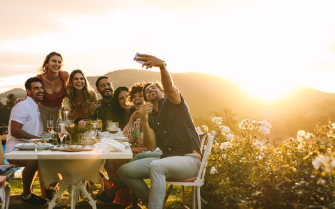 Friends chilling at dinner party taking selfie