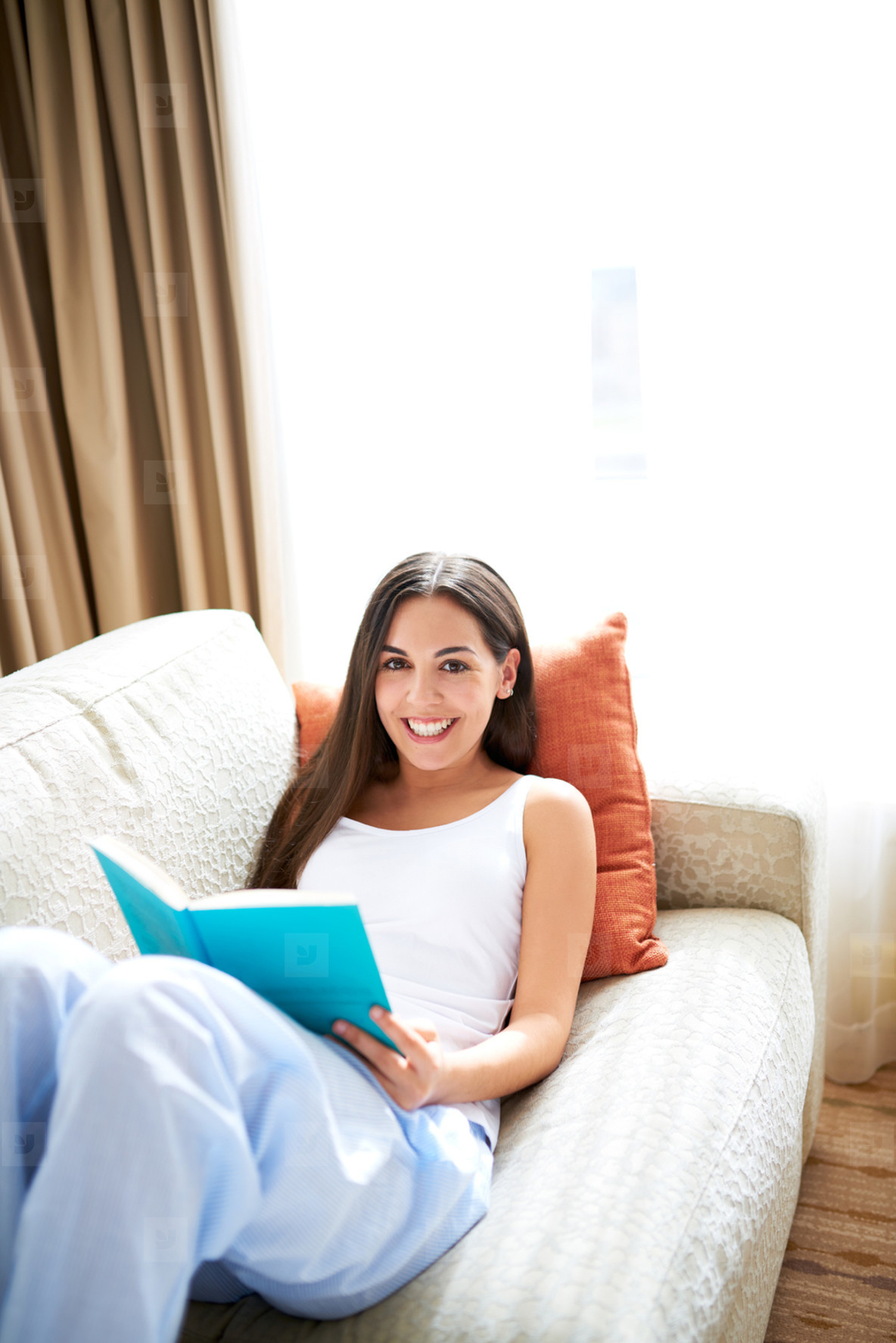 Woman reclining against orange cushion looking up smiling