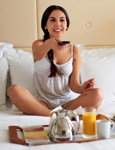 Woman sitting in bed watching television