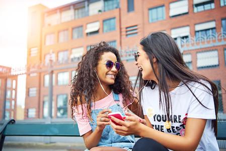 Girlfriends sitting outside listening to music on earphones