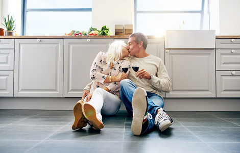 Senior couple kissing and drinking wine in their kitchen