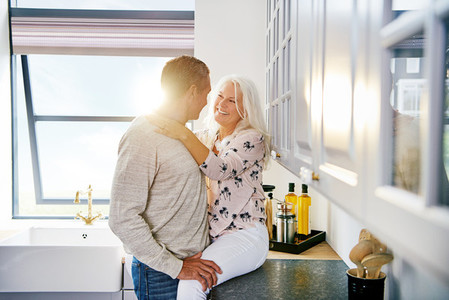 Smiling senior couple sharing a romantic moment in their kitchen