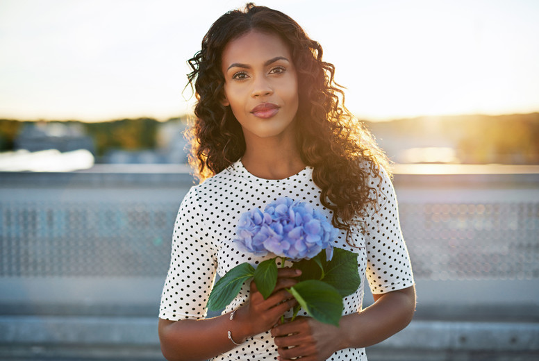 Attractive woman holding a pretty flower