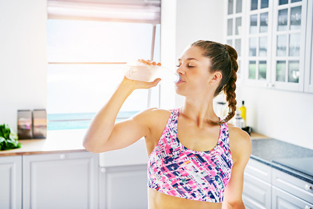 Sportive female drinking water with eyes closed