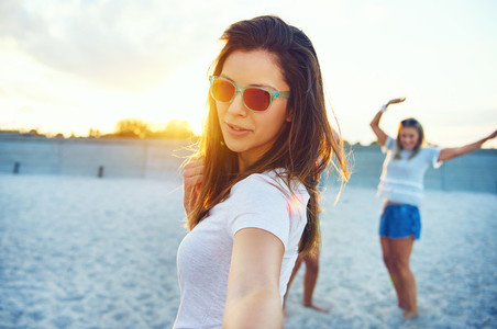 Gorgeous woman in sunglasses dancing on beach