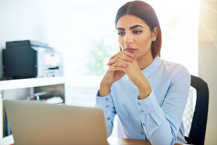 Sad single female with folded hands at laptop