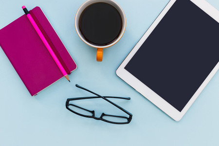 White tablet computer with coffee cup on blue color background r