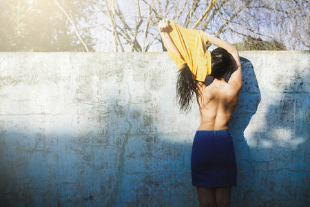 Beautiful brunette against the wall of an empty pool undressing with bare back
