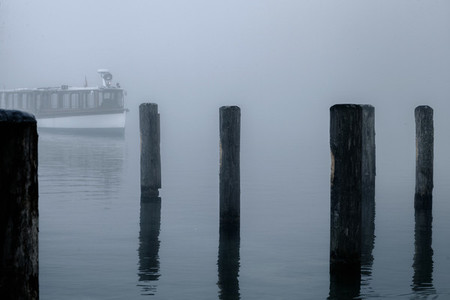 Views of the wooden pier in the mist and a lone boat on the Konigsee lake of Germany