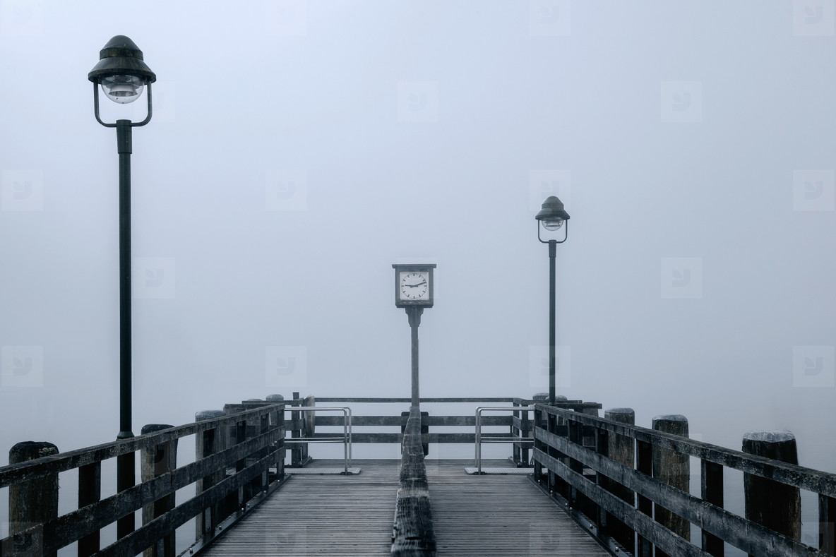 Views of the lonely wooden pier in the fog with two streetlights and ancient clock