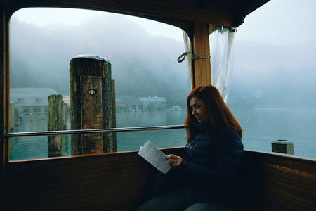 Redhead woman sitting in a boat on a lake with fog