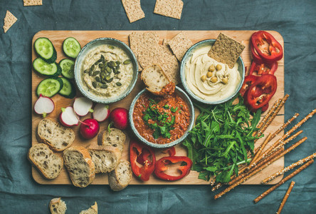 Flat lay of Vegetarian dips hummus babaganush muhammara on wooden board