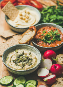 Vegetarian dips hummus  babaganush  muhammara over wooden background