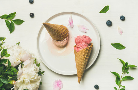 Flat lay of ice cream scoops and peonies on plate