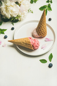 Ice cream scoops and peonies over white background  copy space