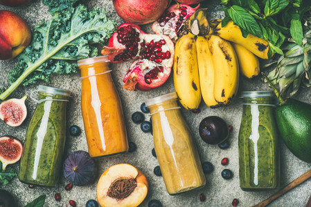 Colorful smoothies in bottles with fresh tropical fruit and vegetables