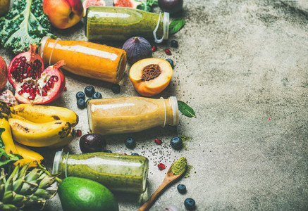 Colorful smoothies in bottles with fresh fruits  copy space