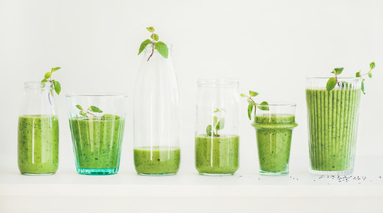 Matcha green smoothie with chia seeds in glasses and bottles