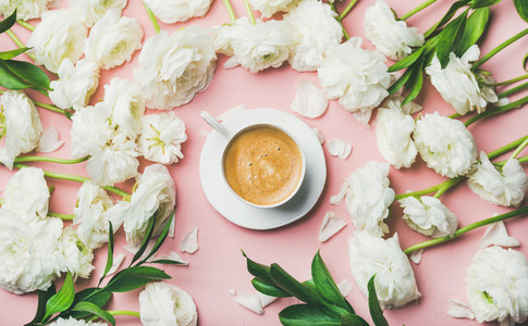 Flat lay of cup of coffee surrounded with white ranunculus flowers
