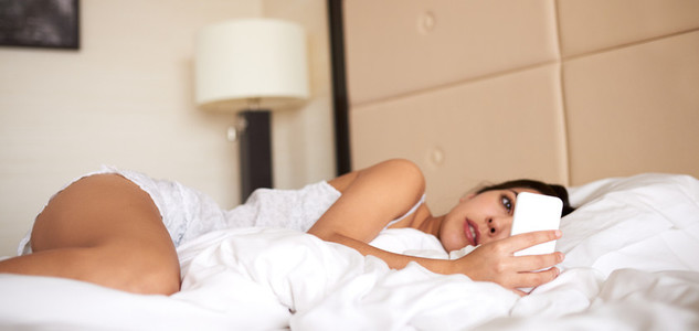 Woman lying in bed looking at cell phone