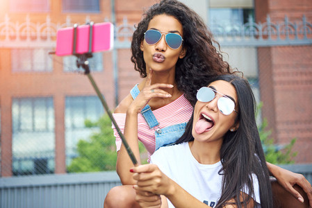 Carefree girlfriends making faces and taking selfies outside