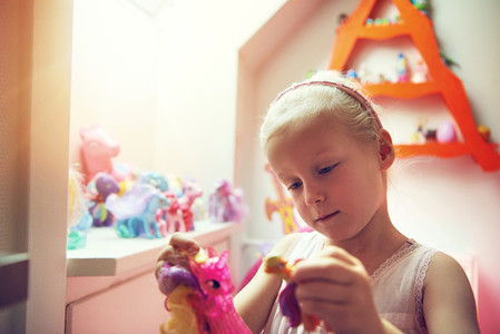 Little child playing with figurines in bedroom