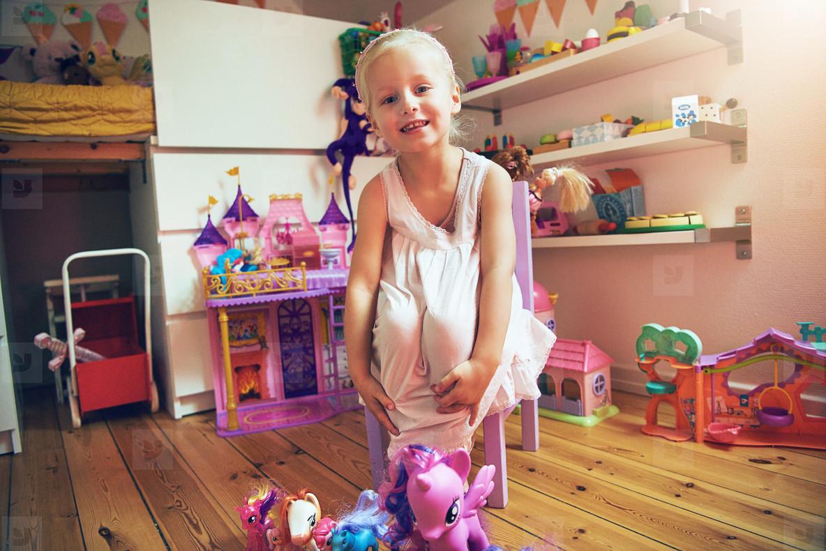 Girl sitting near toys looking at camera